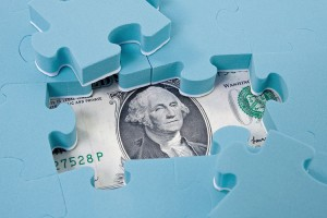 Hidden Assets $100 bill under puzzle pieces [Image © graja - Fotolia.com]